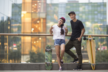 Cheerful young Chinese couple with skateboard dating