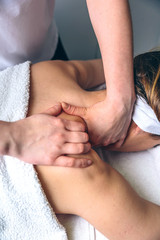 Close up of young woman receiving massage on shoulders in a clinical center. Medicine, healthcare and beauty concept.