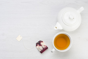 cup of tea with teapot and tea bag on table