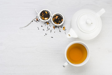 cup of tea with teapot and open infuser with black tea on table