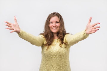 portrait of attractive smiling caucasian woman raised up arms hands at you. She is dressed in yellow sweater. Happy to welcome a friend or guest. I want to hug you.