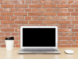 Laptop Computer with blank screen on wooden desk with red bricks wall background