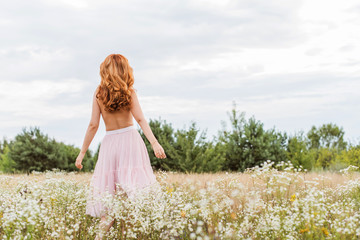 Flowers and romantic woman in the field. Lit evening sun, Beauty Romantic Girl Outdoors. Blowing Long Hair. Autumn. Glow Sun, Sunshine. Toned in warm colors