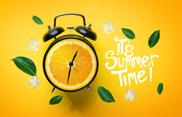 It's Summer Time Typography. Alarm Clock of Orange Fruit Green Leaves and Ice Cube Flying Around on Yellow Background