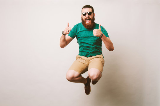 Cheerful bearded hipster man with sunglasses jump over white background and showing thumbs up