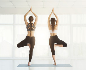 Two women practising yoga together against window