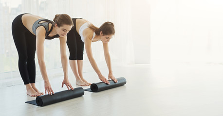 Sporty women rolling up yoga mats after training