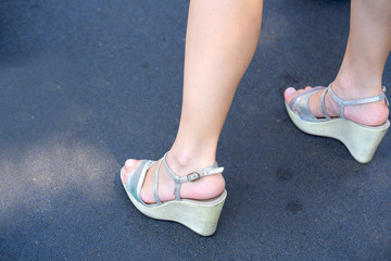 Female legs and gray sandals on a wedge shoes, with beauty feet and legs