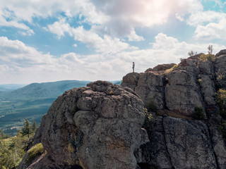 Man is standing on a mountain cliff and looks into the distance. amazing view