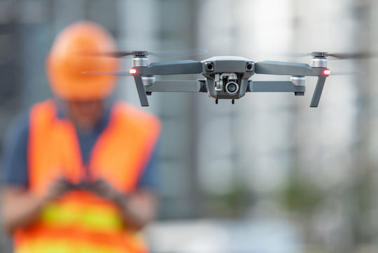 Young Asian engineer flying drone over construction site. Using unmanned aerial vehicle (UAV) for land and building site survey in civil engineering project.