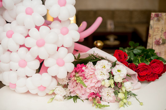 flowers eustoma and rose. A balloon in the form of flowers on a white table