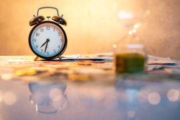 Reflection of clock and blurred hourglass on glowing table with banknotes and coins of international currency. Time investment and passing time. Urgency countdown timer for business deadline concept