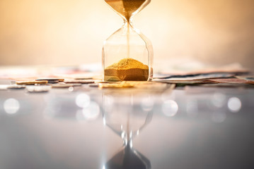 Reflection of brown sand running through the shape of modern hourglass on glowing table with currency. Time investment and passing time. Urgency countdown timer for business deadline concept