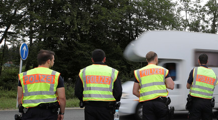 German police officers control cars at a checkpoint between the Austrian and German border in Piding