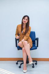 Portrait of beautiful asian business woman wear yellow dress in a office,Thailand people wear ladies uniforms office,Sexy woman on sofa