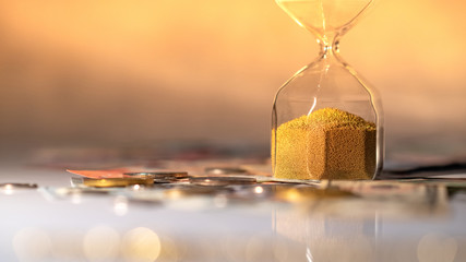 Reflection of hourglass running out of time on glowing table with currency. Time investment and passing time. Urgency countdown timer for business deadline concept