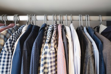 Various shirts hanging in hangers at home