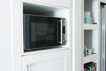 Microwave oven in cabinet at home