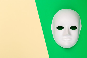 Decorative white mask on color block background top view