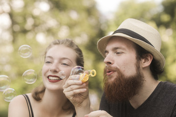 Couple sitting in a park holding a bubble wand blowing bubbles