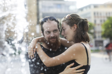 Couple standing by a water fountain hugging