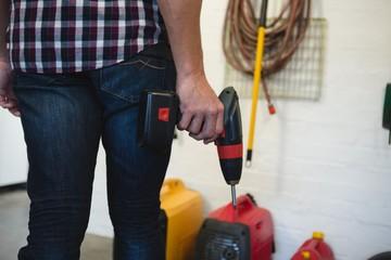 Male carpenter holding drill machine in workshop