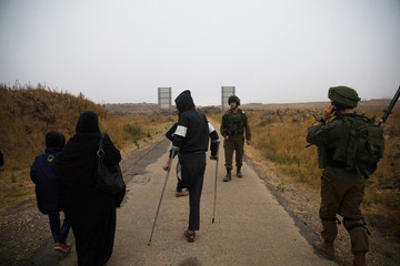 Syrians walk to a bus just after they crossed the armistice line from Syria to the Israeli-occupied Golan Heights to get medical treatment in Israel