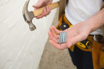 Male carpenter holding hammer and nails