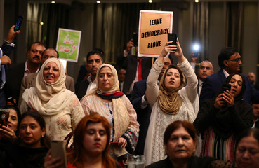People hold banners as ousted Prime Minister of Pakistan, Nawaz Sharif, appears with his daughter Maryam, at a news conference at a hotel in London