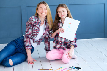 family leisure. mom and daughter drawing together at home. parenting moments. girl showing the finished picture