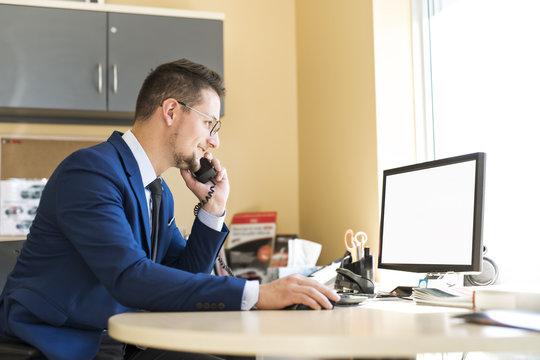 Business man working at a car dealer smiling