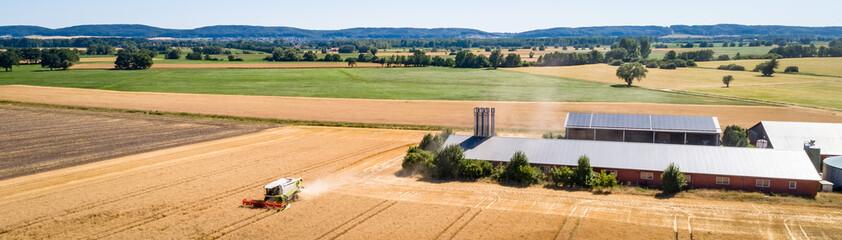 Luftbild - Getreideernte im Mittelgebirgsraum,Mähdrescher vor einer Schweinemastanlage