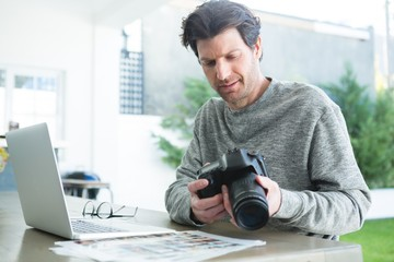 Man using laptop and holding digital camera