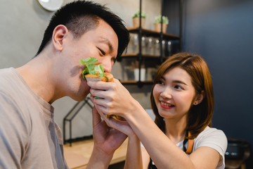 Beautiful happy asian couple are feeding each other in the kitchen. Young asian man and woman have romantic time while staying at home. Couple lifestyle at home concept.