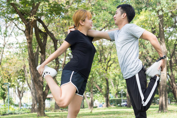 Asian young love couple workout on stretching their bodies together to be prepared for the exercise in the warm afternoon in the the park surrounded with green trees. Couple outdoor exercise together.