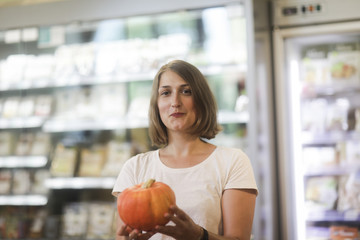 Woman standing in a supermarket choosing a pumpkin