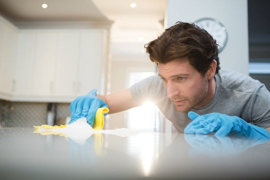 Man cleaning kitchen worktop at home
