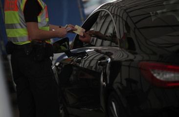A German police officer controls a car at a checkpoint between the Austrian and German border in Kiefersfelden