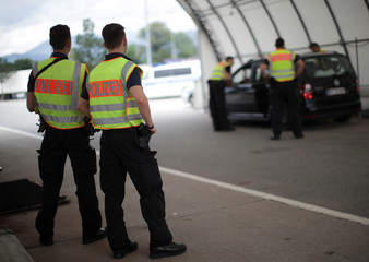 German police officers control a car at a checkpoint between the Austrian and German border in Kiefersfelden
