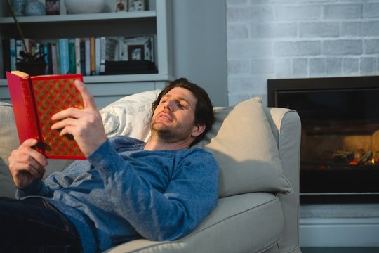 Man reading a book while lying on sofa in living room