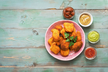 Chicken nuggets on a wooden green rustic table with a variety of sauces. Flat lay,copy space.