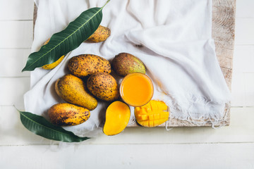 nature mango and mango juice On a wooden table and a white cloth