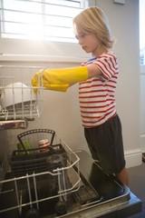 Boy arranging utensils in kitchen trolley