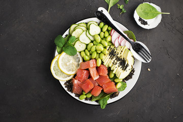 Fresh seafood kitchen. Poke a bowl of salmon, avocado, soybeans, cucumbers, radish, micro greens, sesame, wild rice. Top View.
