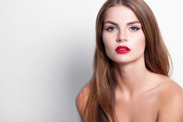 Close-up fashion portrait of young beautiful woman with Hollywood make up, red lips and fair hair in studio. Naked shoulders.