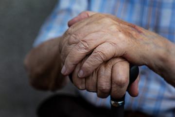 Haende einer älteren Person mit Gehstock