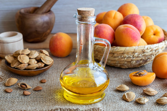A bottle of apricot kernel oil with fresh apricots
