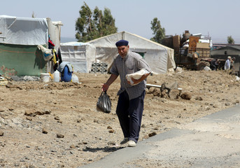 Internally displaced man holds a stack of bread near the Israeli-occupied Golan Heights in Quneitra