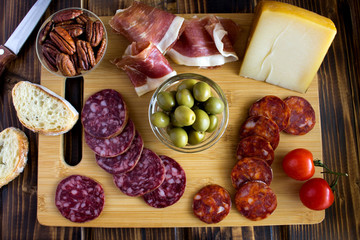 Spanish jamon,sausage and cheese in the cutting board on the  brown  wooden background.Top view.
