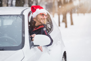 Man wearing Santa Claus hat and leaning on car window. Winter travel concept.